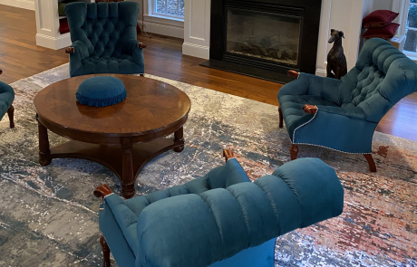 Blue upholstered chairs around the fireplace table